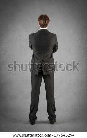 Young businessman full body portrait from behind against grunge background.  - stock photo