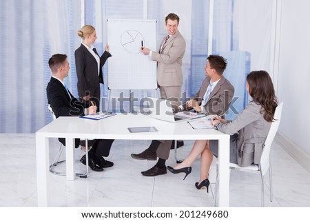 Young businessman giving presentation to colleagues in conference room - stock photo