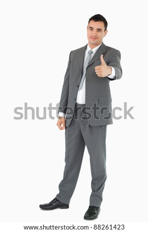 Young businessman giving thumb up against a white background