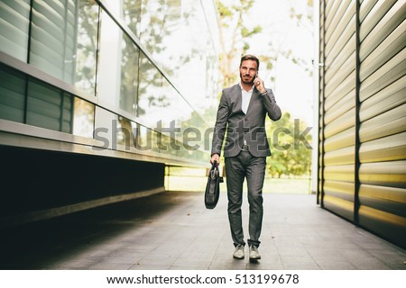 Young businessman going to work, talking on mobile phone and carries a briefcase in hand