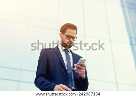 Young businessman had just received bad news as he reads a text message on cell phone - stock photo
