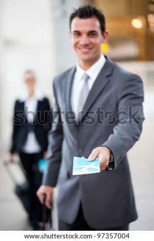 young businessman handing over air ticket, focus on ticket - stock photo