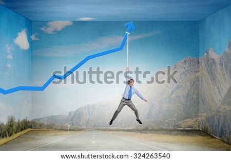 Young businessman hanging on increasing blue graph - stock photo