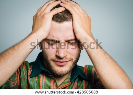 young businessman has a headache, migraine, isolated on a gray background - stock photo