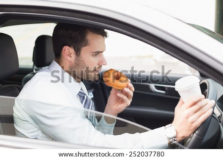 Young businessman having coffee and doughnut in his car - stock photo