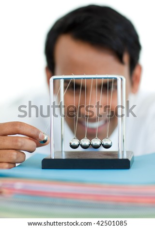 Young businessman having fun with kinetic balls at work - stock photo