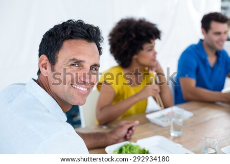 Young businessman having lunch with his colleagues - stock photo
