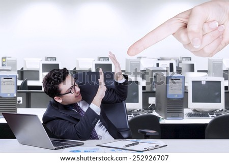 Young businessman having problem in the office and bullied by someone
