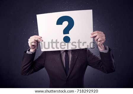 Young businessman hiding behind a question mark drawn on paper