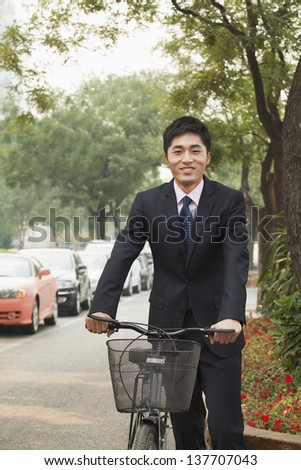 Young businessman holding a bicycle on a city street in Beijing