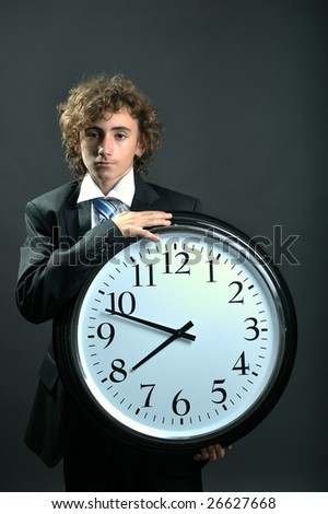 Young businessman holding a big clock in hands