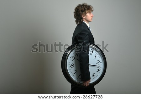 Young businessman holding a big clock in hands, deadline concept - stock photo