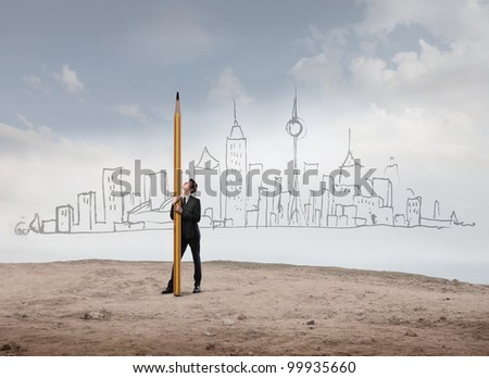 Young businessman holding a big pencil with hand-drawn skyline of a big city in the background - stock photo