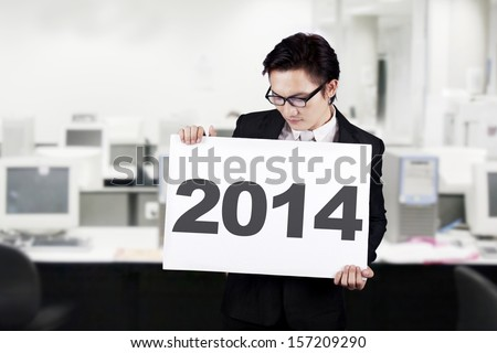 Young businessman holding a 2014 billboard on office - stock photo