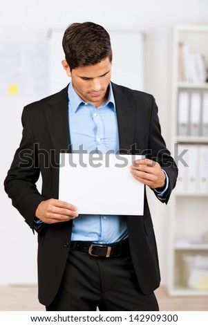 Young businessman holding a blank white paper and looking down. - stock photo