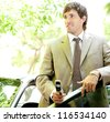 Young businessman holding a cell phone while leaning on his car door while in a leafy street. - stock photo