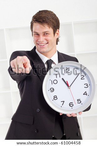 young businessman holding a clock in office - stock photo