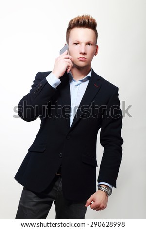 Young businessman holding a mobile phone and looking confused against white - stock photo