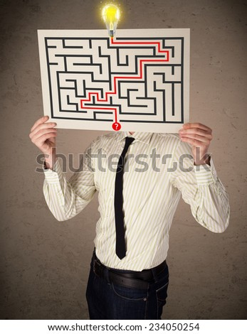 Young businessman holding a paper with a labyrinth on it in front of his head - stock photo