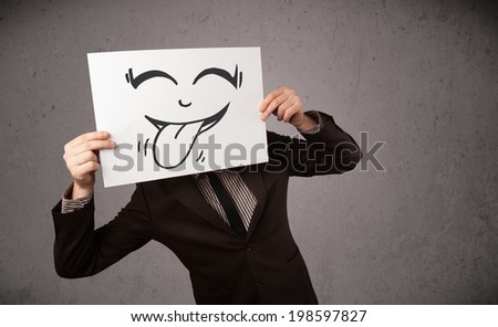 Young businessman holding a paper with funny smiley face on it in front of his head
