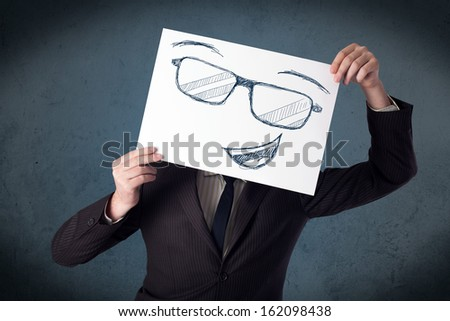 Young businessman holding a paper with smiley face in front of his head