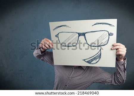 Young businessman holding a paper with smiley face in front of his head - stock photo