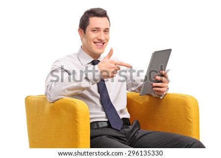 Young businessman holding a tablet and pointing with his finger towards it seated in a yellow armchair isolated on white background - stock photo
