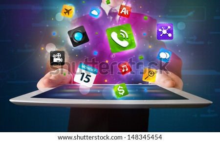 Young businessman holding a tablet with modern colorful apps and icons - stock photo