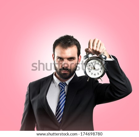 Young businessman holding an antique clock over pink background  - stock photo
