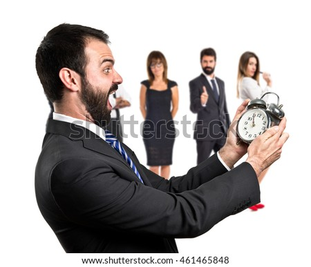 Young businessman holding an antique clock with many people behind