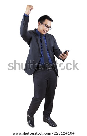 Young businessman holding and looking at smartphone while celebrate his success - stock photo