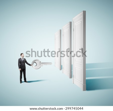 young businessman holding big key with closed doors - stock photo