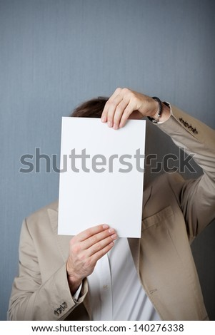Young businessman holding blank paper in front of face against blue wall - stock photo