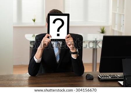 Young Businessman Holding Board With Question Mark In Front Of Face At Desk - stock photo