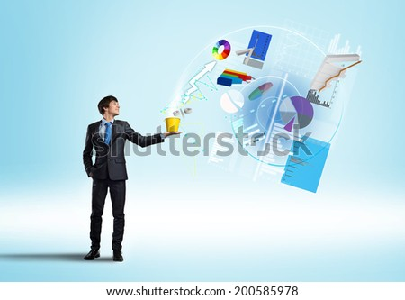 Young businessman holding bucket with graphs and diagrams flying out