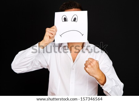 Young businessman holding card with a angry face - stock photo