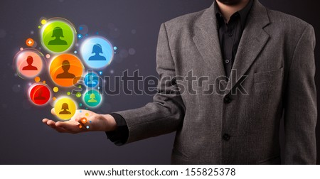 Young businessman holding colorful social network icons in his hand - stock photo