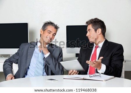 Young businessman holding digital tablet sitting with colleague at desk in office - stock photo
