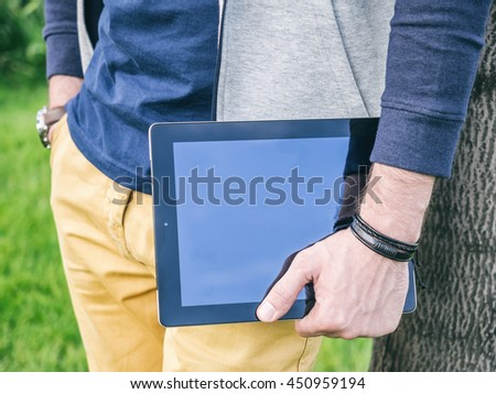 Young Businessman holding digital tablet with blank screen in hand