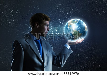 Young businessman holding Earth planet in palm. Elements of this image are furnished by NASA - stock photo