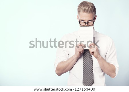 Young businessman holding empty notebook with space for text, partially covering his face, isolated. - stock photo