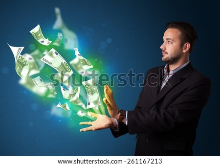 Young businessman holding glowing paper moneys in his hand
