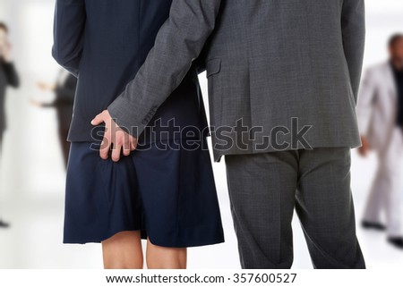 Young businessman holding hand on his beautiful partners ass