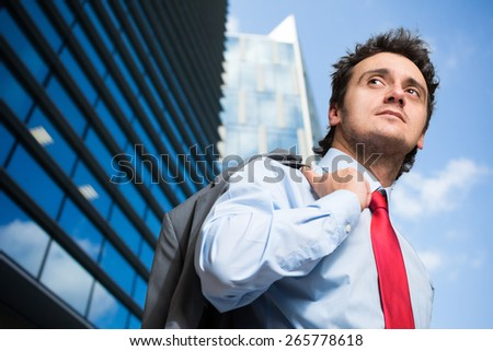 Young businessman holding his jacket outdoor - stock photo