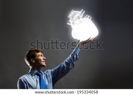 Young businessman holding human 3d heart in palm - stock photo