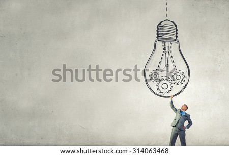 Young businessman holding in hands big light bulb - stock photo