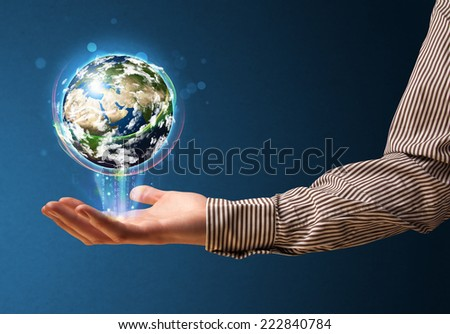 Young businessman holding in his hand a glowing earth globe, Elements of this image furnished by NASA - stock photo
