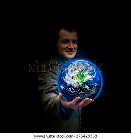 Young businessman holding in his hand a glowing earth globe. Elements of this image furnished by NASA. - stock photo