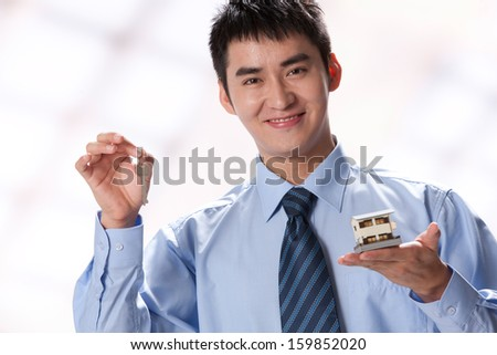 Young businessman holding key and artificial house - stock photo