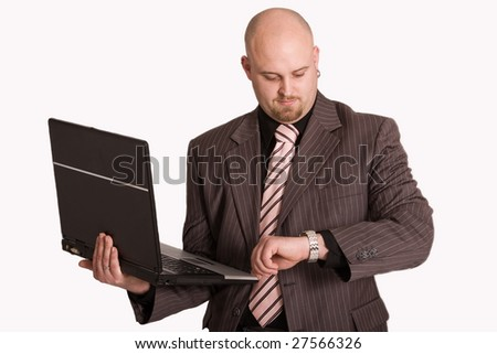 Young businessman holding laptop checking the time - stock photo